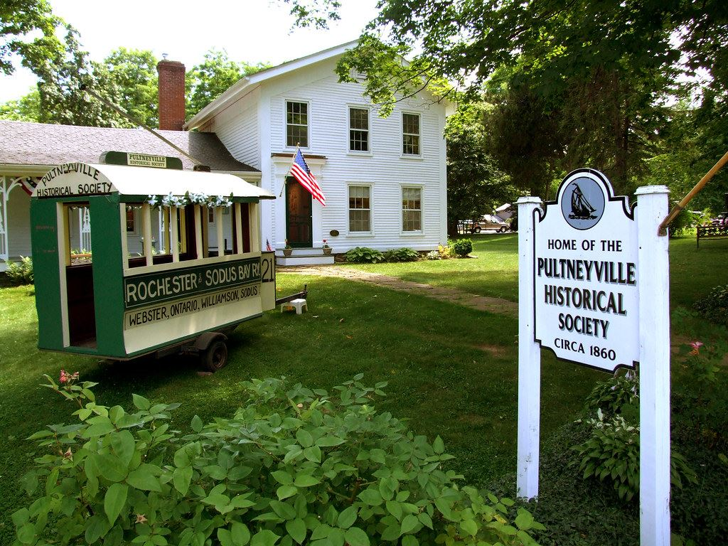 Summertime exterior image of an early 19th century building with Willaims-Pultneyville Historical Society sign out front