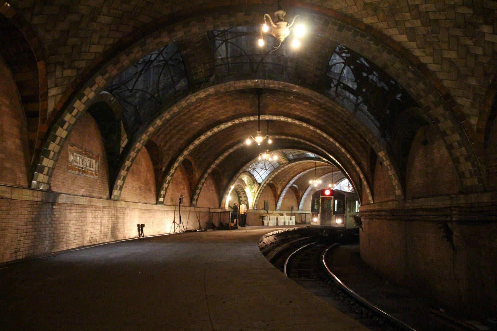 Inside what looks as an old subway stop with large archways and classic subway tile. A subway train car can be seen in the distance.